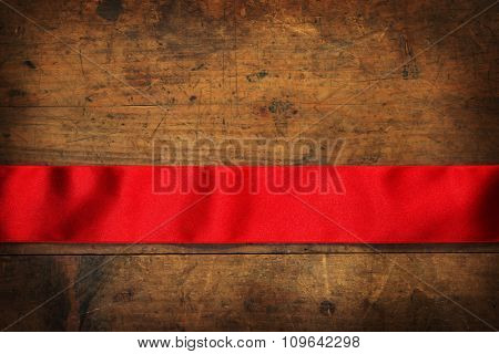Red ribbon and rustic wooden background. Red ribbon horizontally placed on a rustic wooden surface. Intentionally shot with low key shadows.