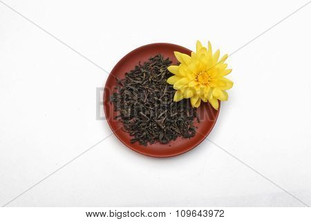 Tea leaves with yellow flower on ceramic saucer