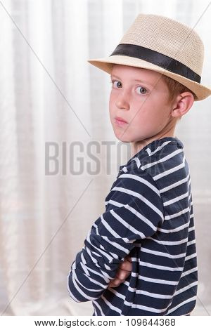 Young Boy With Hat Looking Angry Into The Camera