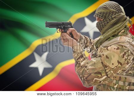Male With Gun In Hand And National Flag On Background - Saint Kitts And Nevis