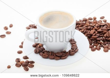 white cup with coffee beans. background
