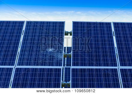 broken of splitted or cracked solar panel among whole panels against a blue sky toned in blue close-up