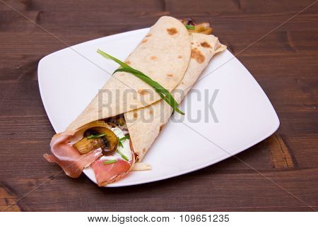 Flatbread with bacon and mushrooms on wood