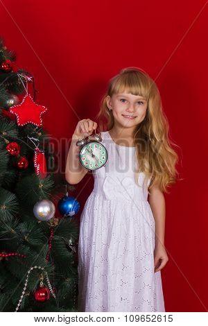 Beautiful baby gir near the Christmas tree in New Year's Eve