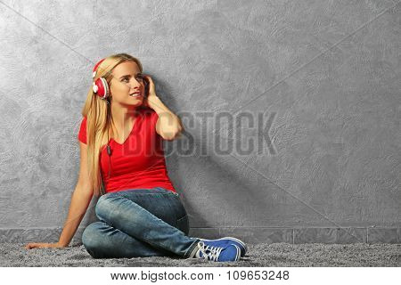 Young woman sitting on the floor and listening to music on a grey wall background