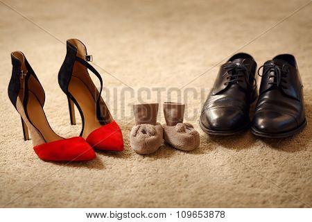 Baby booties between parent's shoes