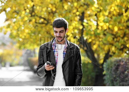 Young man in a park listening to music