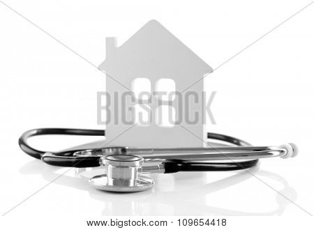 Concept of family medicine - white mini house and stethoscope isolated on white background