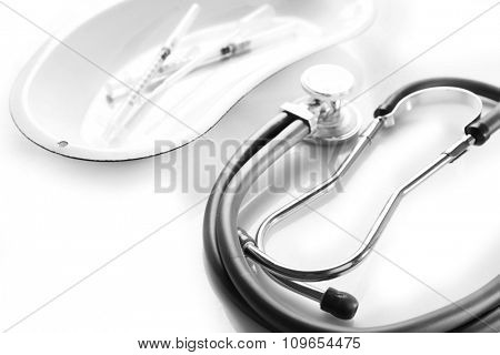 Stethoscope with syringes in a bowl on white background, close up