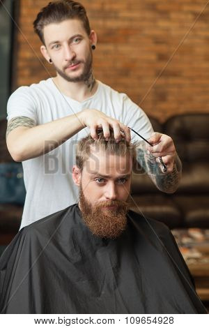 Cheerful young bearded hipster is attending a hairstylist