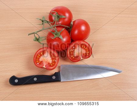 Kitchen knife and tomato on wooden table