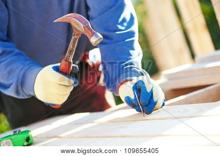 A closeup of male carpenter worker hands hammering nail into board outdoors