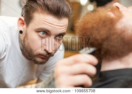 Skillful male hairstylist is working at beauty shop