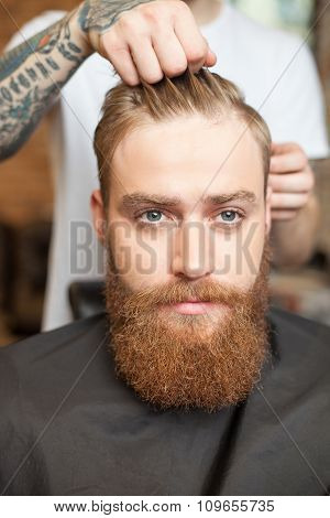 Handsome bearded guy is attending the hairdresser