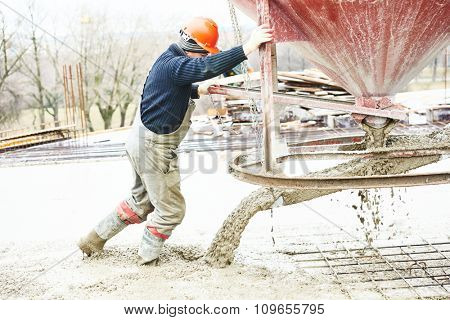 Concreting work. Construction site worker during concrete pouring into formwork at building area with barrel skip