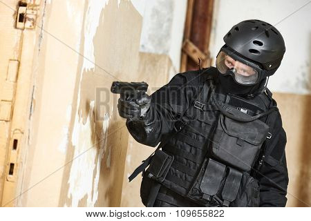 Military industry. Special forces or anti-terrorist police soldier armed with pistol ready to attack during clean-up operation