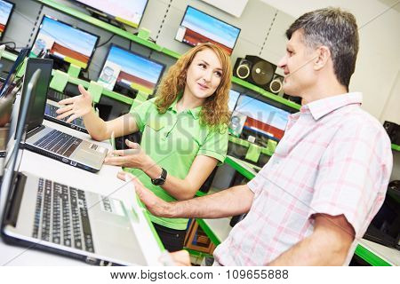 Shopping concept. Happy seller assistant woman help purchaser choosing notebook computer in electronics supermarket shop