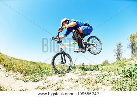 Bicycle extreme sport jump. Young cyclist high jumping downhill on the mountain bike ar cross-country