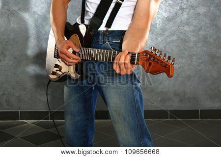 Young man paying guitar closeup