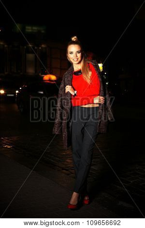 Beautiful stylish young woman walking on the street at night
