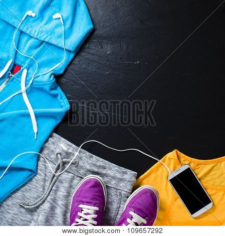 Sport clothes, shoes and mobile phone with headphones. Top view