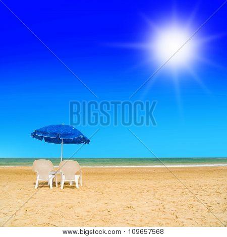 sun loungers and a beach umbrella on a deserted beach