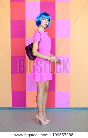 Young woman in mini dress posing like doll on bright wall background