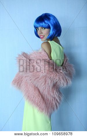 Young woman with blue hairstyle on light wall background