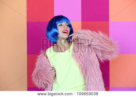 Young woman with blue hair on bright wall background