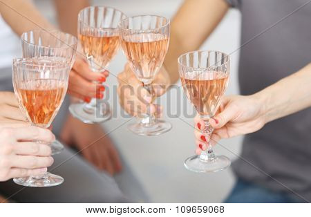 Friends hands with glasses of pink wine, close up