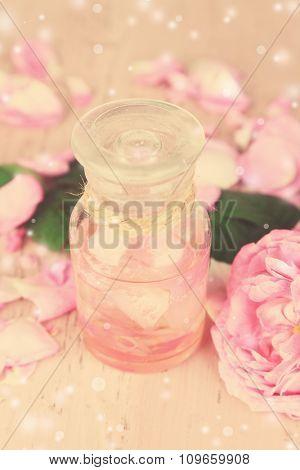 Rose oil in bottle on light background