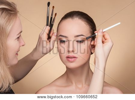 Professional beautician is working with the model