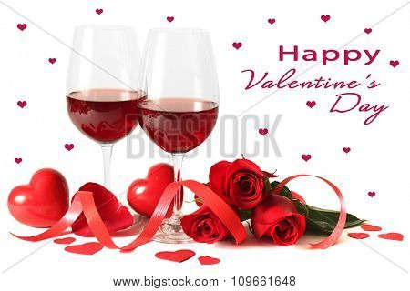 Composition with red wine in glasses, red roses and decorative hearts on light background