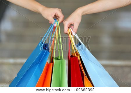 Female hands holding shopping bags close up