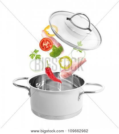 Fresh vegetables falling into a casserole pot isolated on white