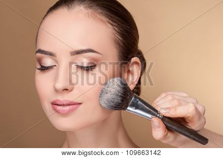 Skillful young beautician is serving her customer
