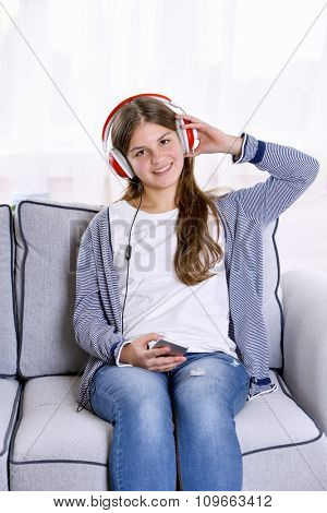 Young pretty girl listening to music on the sofa in her room