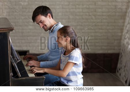 Musician teacher and little girl play piano together