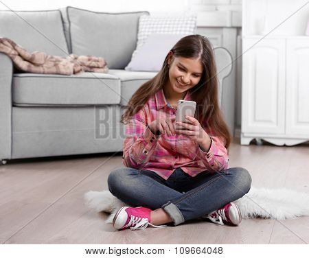 Young pretty girl sitting on the floor and using the phone in her room