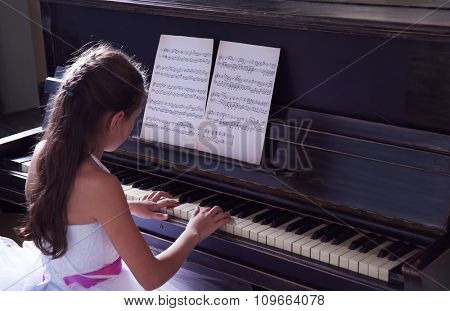 Cute little princess girl plays piano in the studio