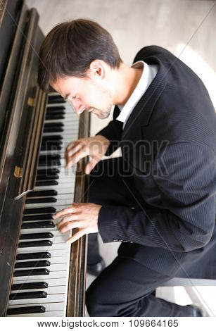 Handsome man in black suit plays piano in the class