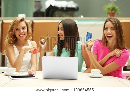 Beautiful young women with laptop and credit card in cafe