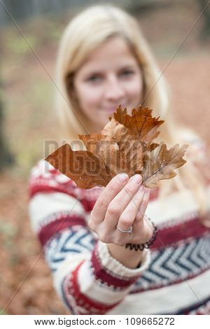 Smiling blonde woman holding leaves in front of her face and looking at camera. Outdoor in the forest.