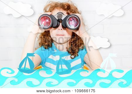 Little Girl Sitting At A Table Looking Through Binoculars