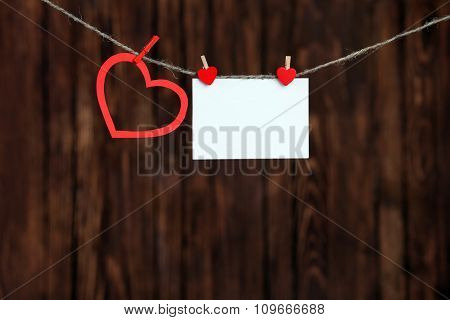 Red heart and blank note, on wooden background