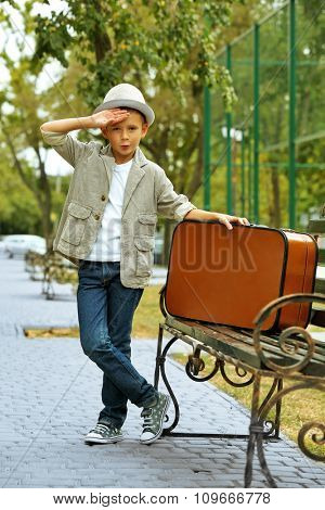 Little boy with suitcase on bench in the park