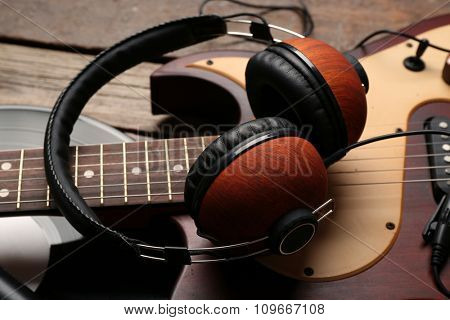 Electric guitar and headphones with vinyl on wooden background
