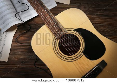 Guitar with music sheets on wooden background
