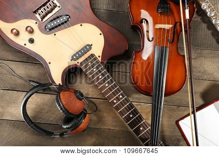 Electric guitar, violin, soprano saxophone, headphones and book on wooden background
