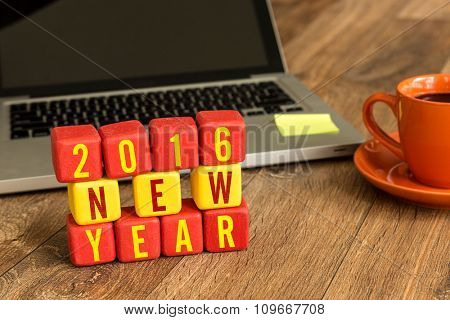 2016 New Year written on a wooden cube in a office desk